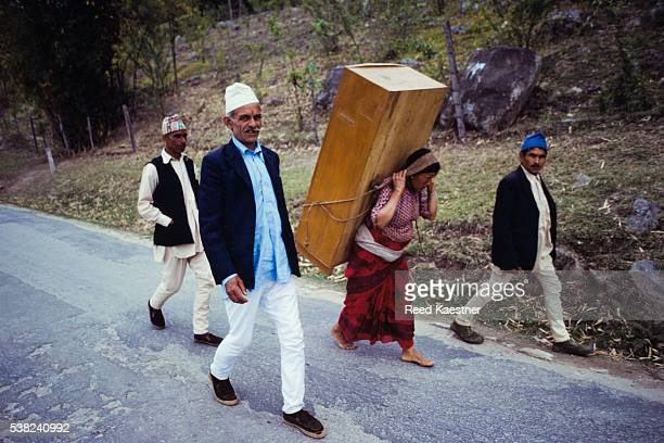 Woman carrying large piece of furniture along roadway.