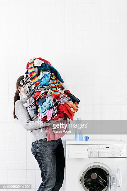 Woman carrying large pile of laundry to washing machine
