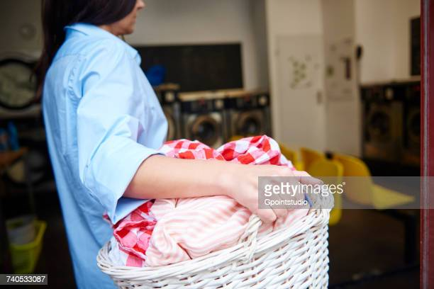 Woman carrying laundry basket in laundrette