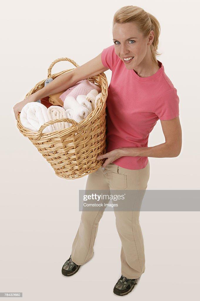 Woman carrying laundry basket : Stockfoto
