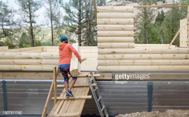 woman carrying log to build cabin in colorado usa - american culture stock pictures, royalty-free photos & images