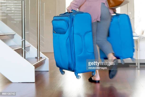 Woman carrying luggage down stairs.