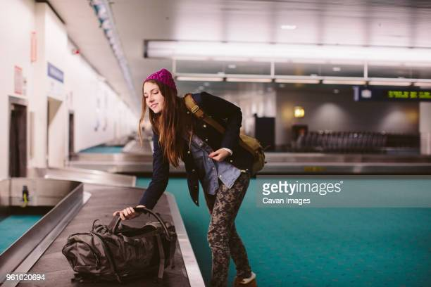 woman carrying luggage from baggage claim at airport - baggage claim stock pictures, royalty-free photos & images