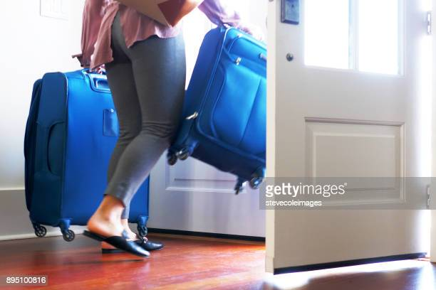 Woman carrying luggage out front door of home.