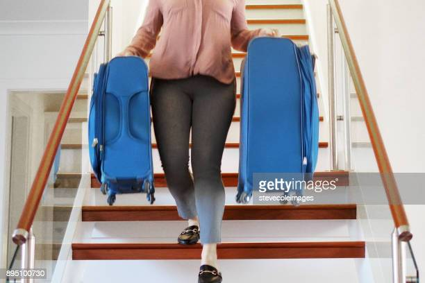 Woman carrying luggage up down stairs.