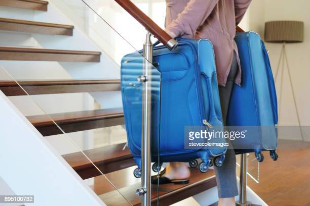 Woman carrying luggage up stairs.