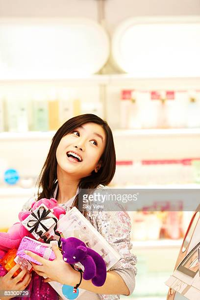 woman carrying many items in retail store - à profusion photos et images de collection