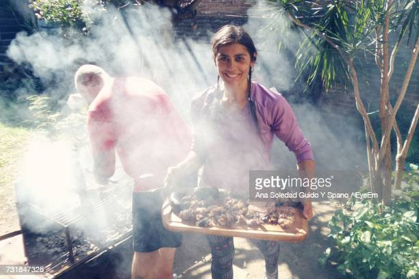 Woman Carrying Meat In Tray While Man Standing By Barbecue In Yard