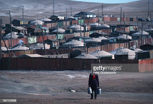 A woman carrying milk churns walks back to her community of traditional tented residences on the outskirts of a town near Ulan Bator These tentlike...