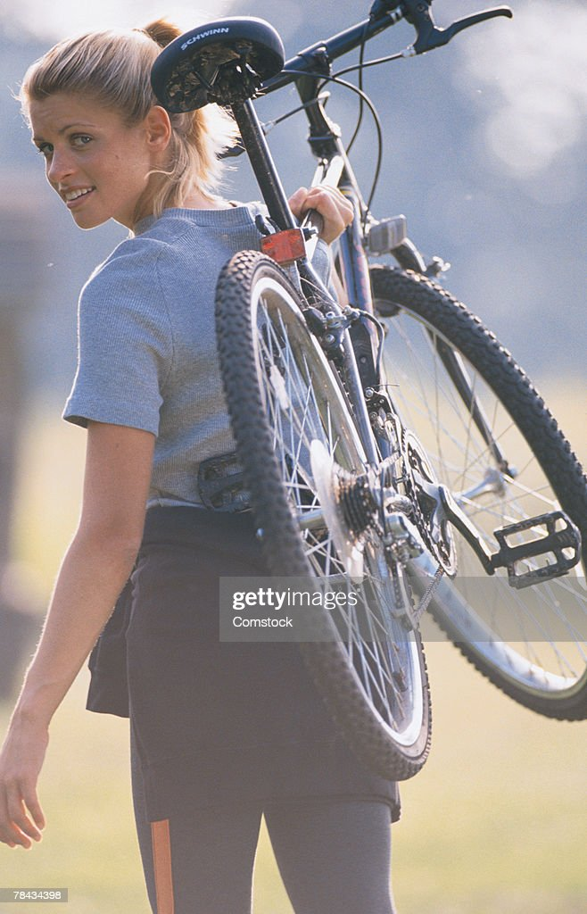 Woman carrying mountain bike , looking over shoulder : Stockfoto