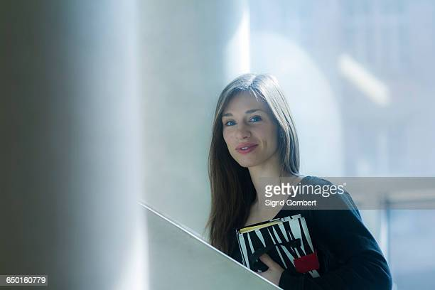 woman carrying notebook looking at camera smiling - sigrid gombert stock pictures, royalty-free photos & images