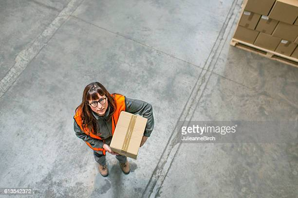 Woman carrying parcel in warehouse