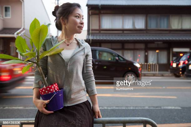 Woman carrying plant