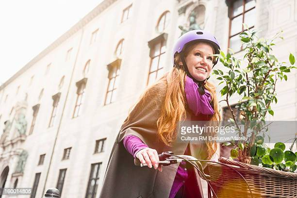 Woman carrying plants in bicycle basket