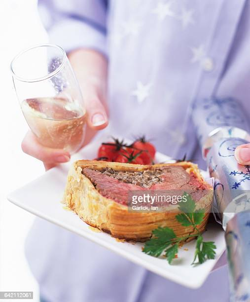 Woman carrying plate of beef Wellington, sparkling wine & cracker