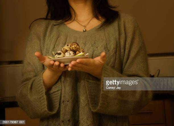 Woman carrying plate of quail's eggs, mid section