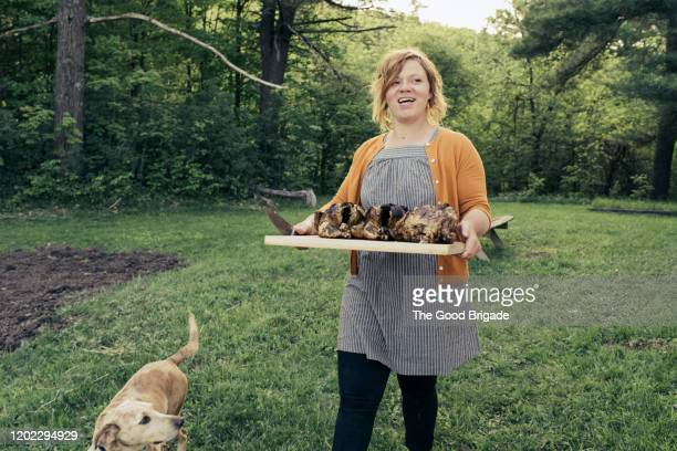 woman carrying platter of grilled chicken at backyard party - poulet grillé photos et images de collection