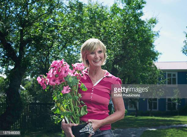Woman carrying potted flowers outdoors