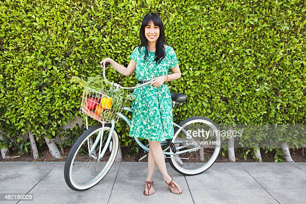 Woman carrying produce in bicycle basket
