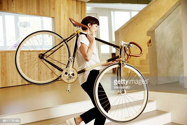 Woman carrying racing cycle on her shoulder in an office