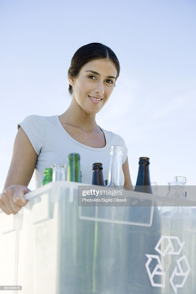Woman carrying recycling bin filled with glass bottles, smiling at camera : Stock Photo