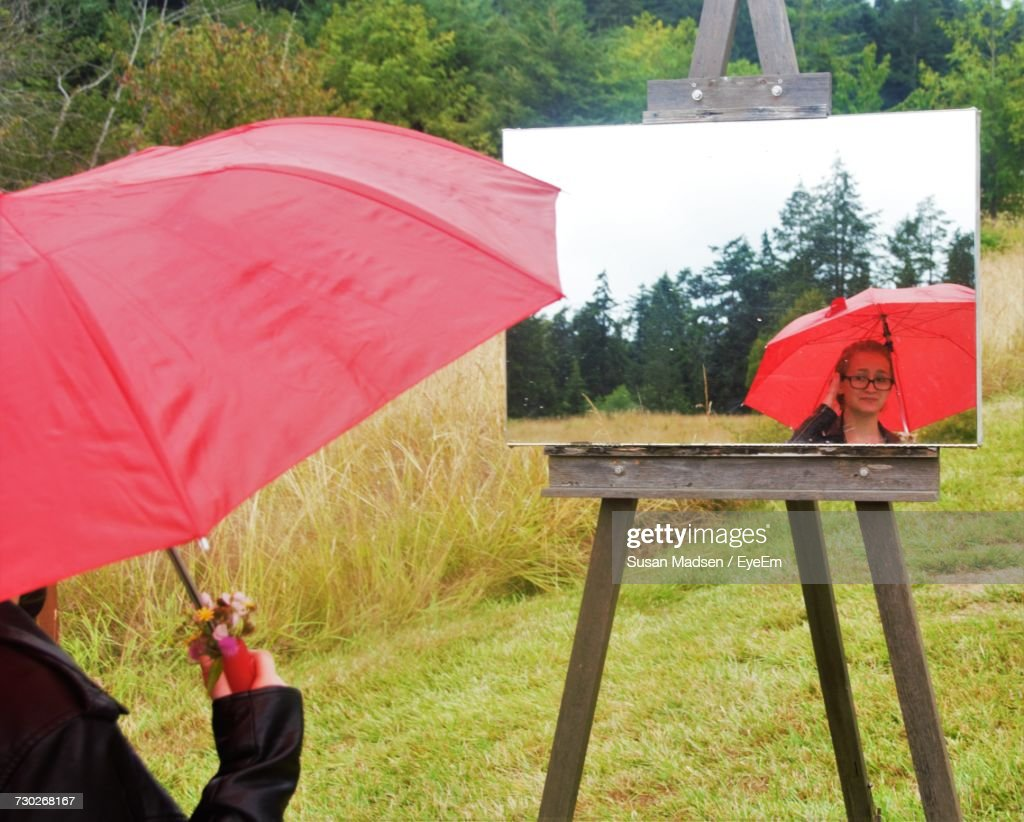 Woman Carrying Red Umbrella Reflecting In Mirror On Grassy Field : Stock-Foto