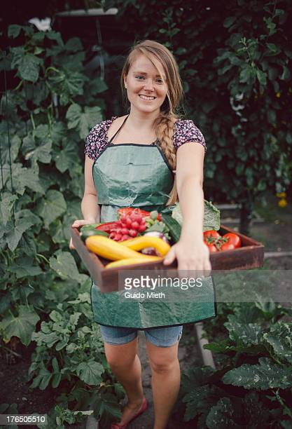 Woman carrying ripe vegetables in garden