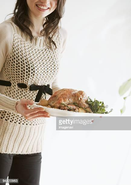 A woman carrying roast turkey