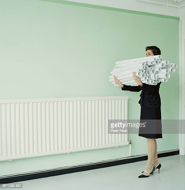 Woman carrying rolls of paper