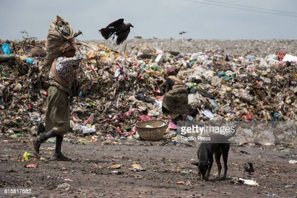 A woman carrying sack og reusable things in the dump site to sell them although it will earn them less than $3 a day Hundreds gather each morning at...