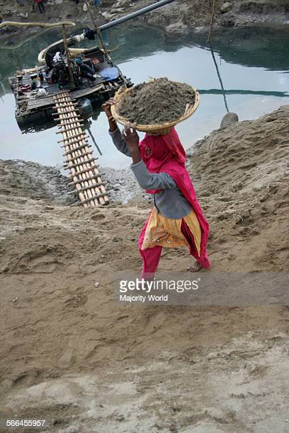 A woman carrying sand from a stone quarry on the bank of Dauki river in Jaflong Sylhet Bangladesh January 18 2010