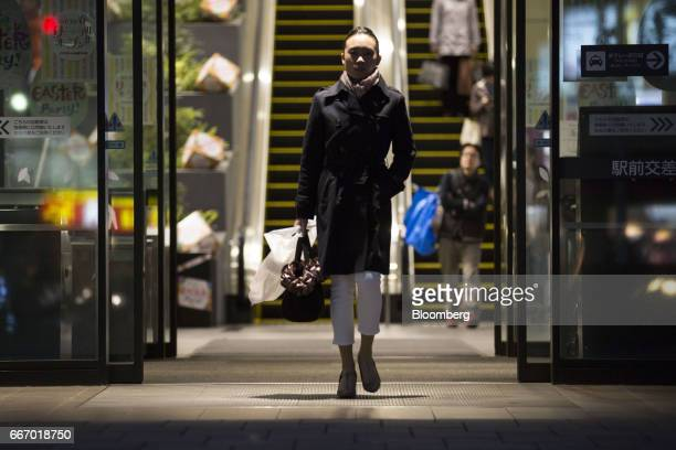 A woman carrying shopping bag leaves an Aeon shopping mall operated by Aeon Mall Co a unit of Aeon Co in Tokyo Japan on Monday April 10 2017 Aeon Co...