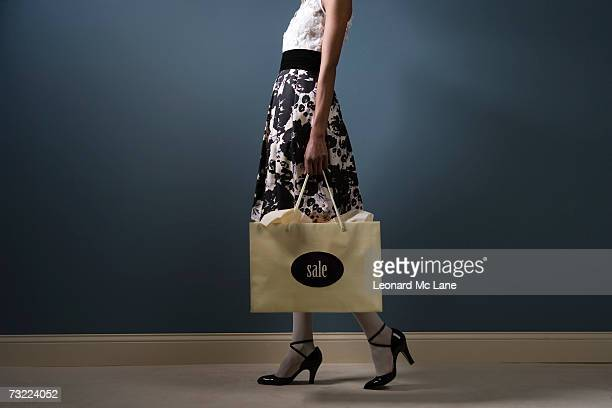 Woman carrying shopping bag, low section