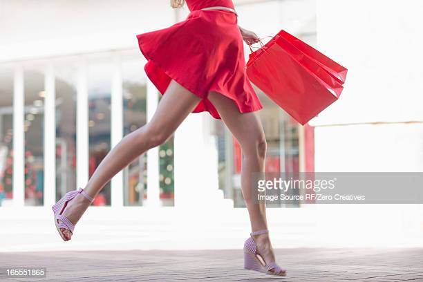 woman carrying shopping bag outdoors - beautiful legs in high heels stock photos and pictures