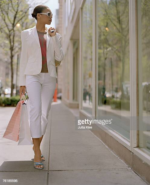 Woman carrying shopping bags and looking into a shop window