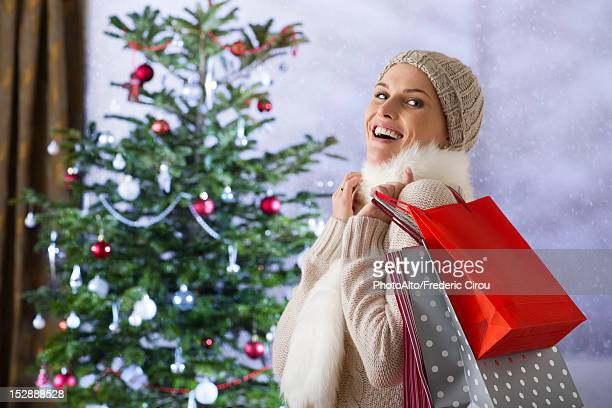 Woman carrying shopping bags, Christmas tree in background