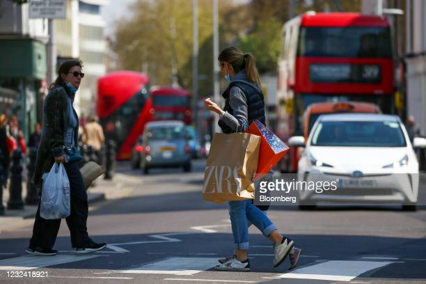 Woman carrying shopping bags crosses the street in the Chelsea district of London, U.K., on Tuesday, April 20, 2021. The U.K. Economy is building...