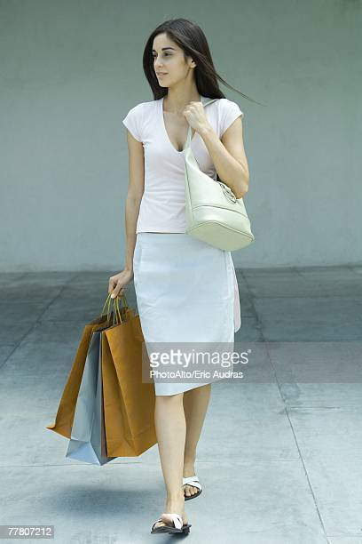 woman carrying shopping bags, full length portrait - long purse stock photos and pictures