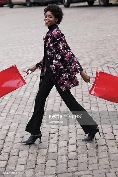 woman carrying shopping bags in city - striding stock pictures, royalty-free photos & images