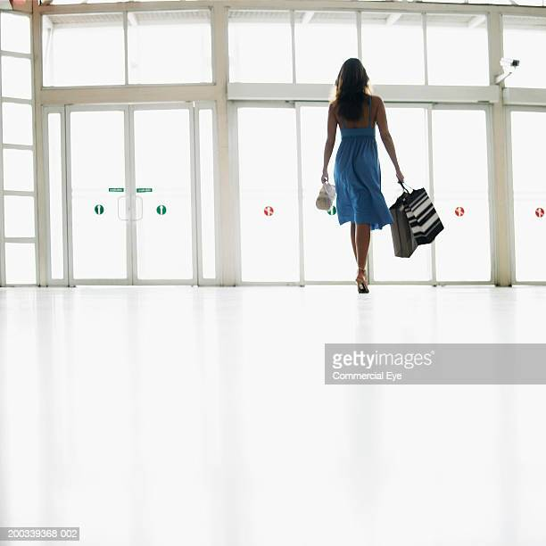 Woman carrying shopping bags in mall, rear view
