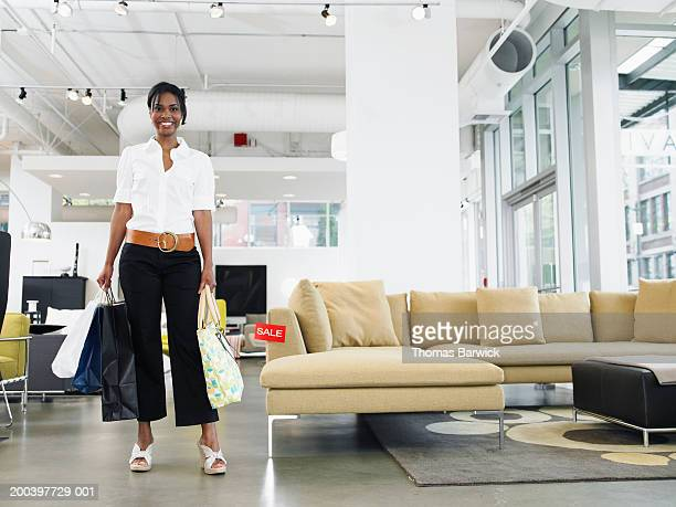 Woman carrying shopping bags in retail furniture store, portrait
