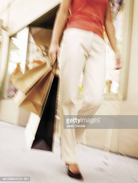 Woman carrying shopping bags in street, low section (defocused, blurred motion)