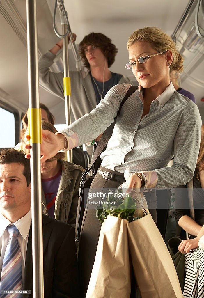 Woman carrying shopping bags on busy bus : Stock Photo