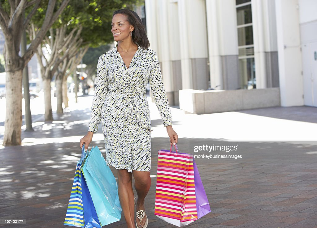 Woman Carrying Shopping Bags On City Street : Stock Photo