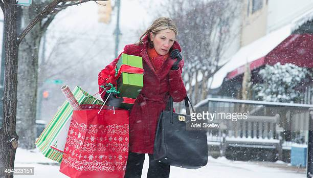 Woman carrying shopping bags on snowy street