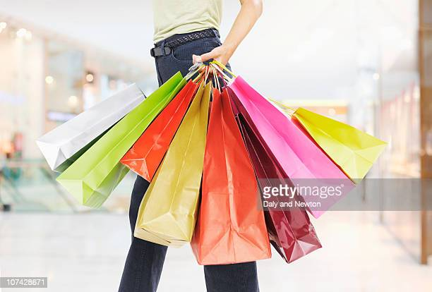 woman carrying shopping bags - consumerism stock pictures, royalty-free photos & images