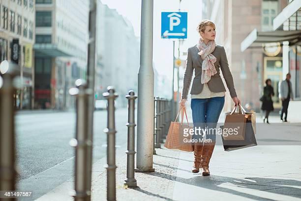 woman carrying shopping bags. - junge frau allein stock-fotos und bilder