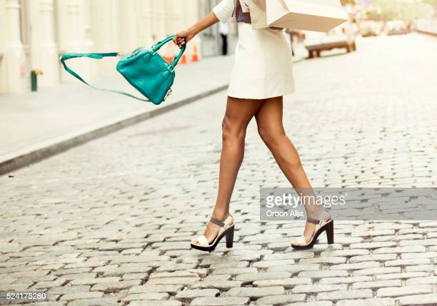 woman carrying shopping bags - black shoe stock pictures, royalty-free photos & images