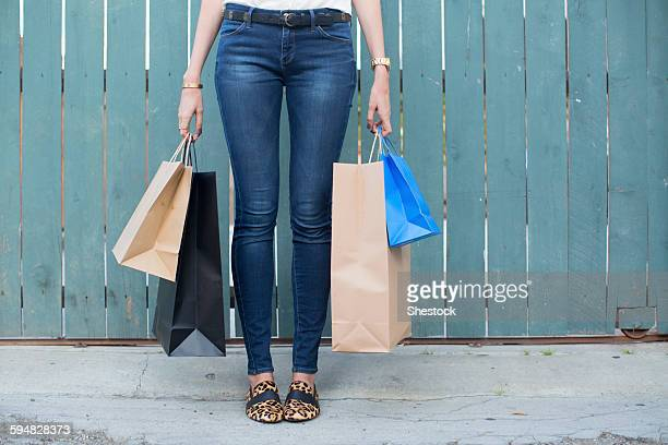 woman carrying shopping bags - jeans stock photos and pictures