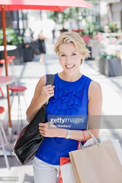 woman carrying shopping bags - alleen één oudere vrouw stockfoto's en -beelden